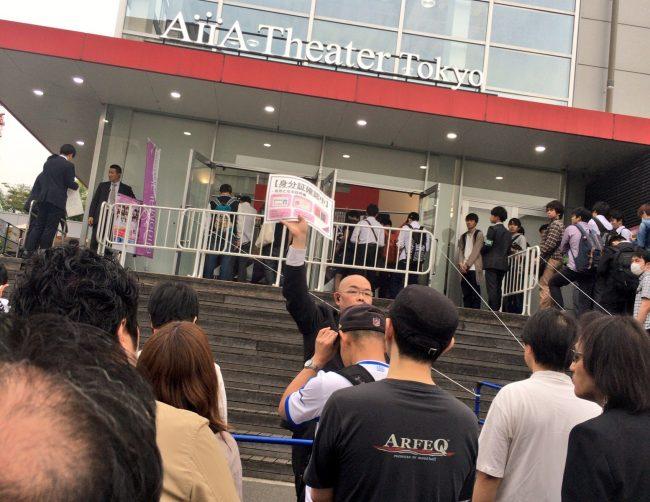 Personal de Nogizaka46 dando la informacion del nuevo requisito de ingreso al auditorio.